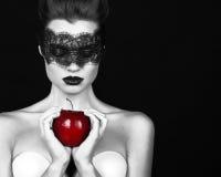 A feiticeira bonita da bruxa da moça com um laço do preto da atadura que guarda a feitiçaria mágica da maçã madura tentou morder  fotografia de stock royalty free