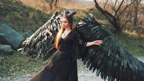 A feiticeira no vestido preto longo do vintage com as luvas do la?o na estrada, guarda suas asas grandes e fortes com m?os delica video estoque