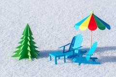 Feito das cadeiras de papel e de um suporte da árvore de Natal na neve Fundo do inverno Imagem de Stock