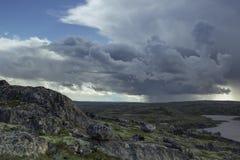 Feixes tormentosos majestosos da nuvem e do sol sobre um lago nas montanhas Fotos de Stock