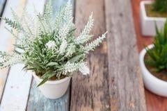 Fejka blomman på den wood plankan arkivfoto