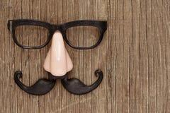 Fejka mustaschen, näsan och glasögon på en träyttersida Arkivfoto