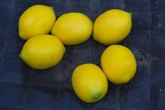 Fejka plast- citroner på den mörka plattan royaltyfria foton