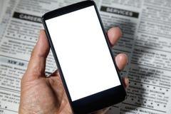 Fejka tidningen och smartphonen Royaltyfria Foton