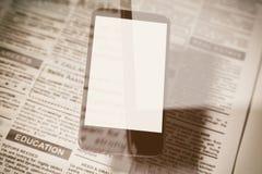 Fejka tidningen och smartphonen Fotografering för Bildbyråer