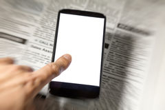 Fejka tidningen och smartphonen Arkivfoto