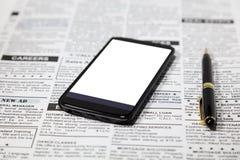 Fejka tidningen och smartphonen Arkivbild