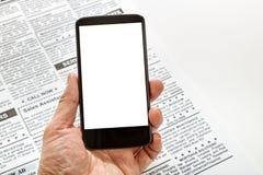Fejka tidningen och smartphonen Arkivfoton