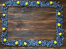 Feld der Blaubeere und der Kirschepflaume auf dunklem hölzernem Hintergrund Stockfotografie