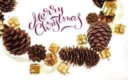 Feld der Kegel und der Geschenke auf weißem Hintergrund mit Text frohen Weihnachten Beschriftungskalligraphie Lizenzfreies Stockfoto