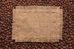 Feld der Leinwand und der Kaffeebohnen, die auf einem weißen Hintergrund liegen Lizenzfreies Stockbild