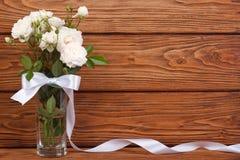 Feld des Blumenstraußes der weißen Rosen und des Bandes Stockfotos