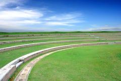 Feld des grünen Grases gegen einen blauen Himmel mit wispy weißen Wolken lizenzfreies stockbild
