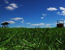 Feld des grünen Grases mit hölzernem ständigem Schwanken und Stapel Heu Lizenzfreie Stockfotografie