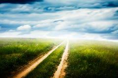 Feld des grünen Grases und des blauen bewölkten Himmels Lizenzfreies Stockfoto