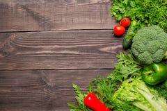 Feld des grünen und roten Frischgemüses auf hölzernem Hintergrund, Draufsicht, Kopienraum stockfotografie
