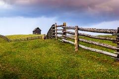 Feld des Grüns mit Holzhaus auf dem Hügel Stockbild