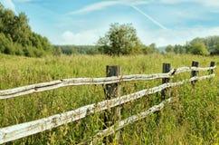 Feld des Grases und des Zauns Lizenzfreie Stockfotografie