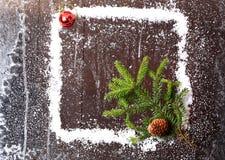 Feld des Schnees mit einem Weihnachtsbaum und ein Stoß auf einer dunklen hölzernen Broschüre des Hintergrundverschneiten winters Lizenzfreie Stockfotos