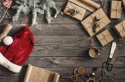 Feld des Weihnachtsgeschenks und des Sankt-Hutes auf Holztisch Stockfotografie