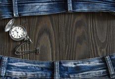 Feld gemacht von den alten getragenen Jeans und von einer Taschenuhr Stockfoto