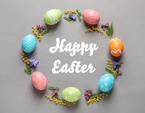 Feld gemacht von den bunten gemalten Eiern und vom Text fröhliche Ostern auf Farbhintergrund stockfoto