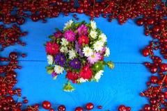 Feld gemacht von der roten Johannisbeere und von der Kirsche mit Blumenblumenstrauß Stockfotografie
