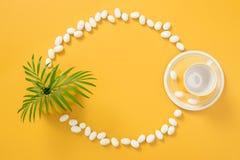 Feld gemacht von der weißen Schokolade, von den Palmblättern und von der gelben Teetasse Stockfotografie