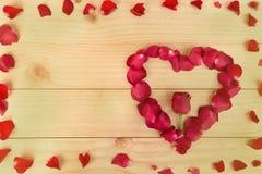 Feld, Herzform gemacht aus rosafarbenen Blumenblättern heraus auf hölzernem Hintergrund, VA lizenzfreie abbildung