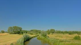 Feld mit Abzugsgraben mit Schilf und Bäume in Natur Kalkense Meersen reerve, Flandern, Belgien Lizenzfreie Stockbilder