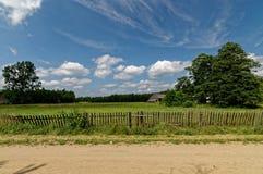 Feld mit Bretterzaun Blauer Himmel mit empfindlichen weißen Wolken Polnische Dorfansicht Lizenzfreies Stockbild