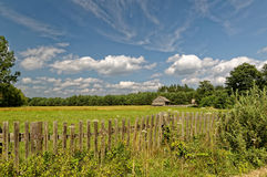 Feld mit Bretterzaun Blauer Himmel mit empfindlichen weißen Wolken Polnische Dorfansicht Stockfotos
