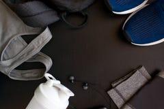 Feld mit dem Bild einer Sportuniform, Schuhe, Rucksack, Oberteile, titsy, Schüttel-Apparat, Kopfhörer lizenzfreie stockfotografie