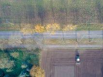 Feld mit gepflogenem Landwirt im Herbst auf einer Landstraße, Bäume wi Lizenzfreies Stockbild