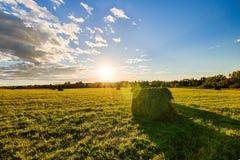 Feld mit Heuschobern bei Sonnenuntergang im Frühherbst Stockbilder
