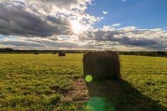 Feld mit Heuschobern bei Sonnenuntergang im Frühherbst Stockbild