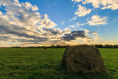 Feld mit Heuschobern bei Sonnenuntergang im Frühherbst Stockfotos