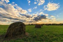 Feld mit Heuschobern bei Sonnenuntergang im Frühherbst Lizenzfreie Stockfotografie