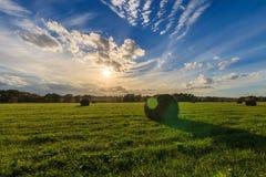 Feld mit Heuschobern bei Sonnenuntergang im Frühherbst Lizenzfreie Stockfotos