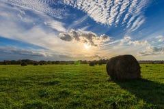 Feld mit Heuschobern bei Sonnenuntergang im Frühherbst Lizenzfreies Stockbild