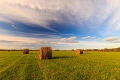 Feld mit Heuschobern bei Sonnenuntergang im Frühherbst Lizenzfreies Stockfoto