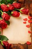 Feld mit roten Rosen und Weinlesepapier stockfoto