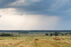 Feld mit Stroh rollt an einem Sommertag Lizenzfreie Stockfotos