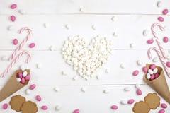 Feld-Süßigkeiten, Plätzchenplätzchen und Eibische in Form von Draufsicht des Herzens weißem hölzernem Hintergrund lizenzfreie stockfotografie