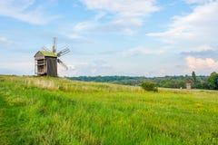 Feld und Windmühle am Himmelsonnenunterganghintergrund Lizenzfreie Stockfotos