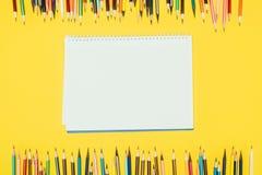 Feld von den bunten Bleistiften lokalisiert auf gelbem Hintergrund mit Notizbuch Lizenzfreies Stockbild