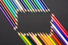 Feld von den farbigen Bleistiften lokalisiert auf schwarzer Pappe Stockfoto