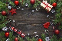Feld von den Kiefernniederlassungen und von den Weihnachtsdekorationen auf dunklem w Lizenzfreies Stockfoto