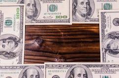 Feld von hundert Dollarscheinen auf Holztisch Beschneidungspfad eingeschlossen Lizenzfreie Stockfotografie
