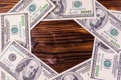 Feld von hundert Dollarscheinen auf Holztisch Beschneidungspfad eingeschlossen Lizenzfreie Stockbilder